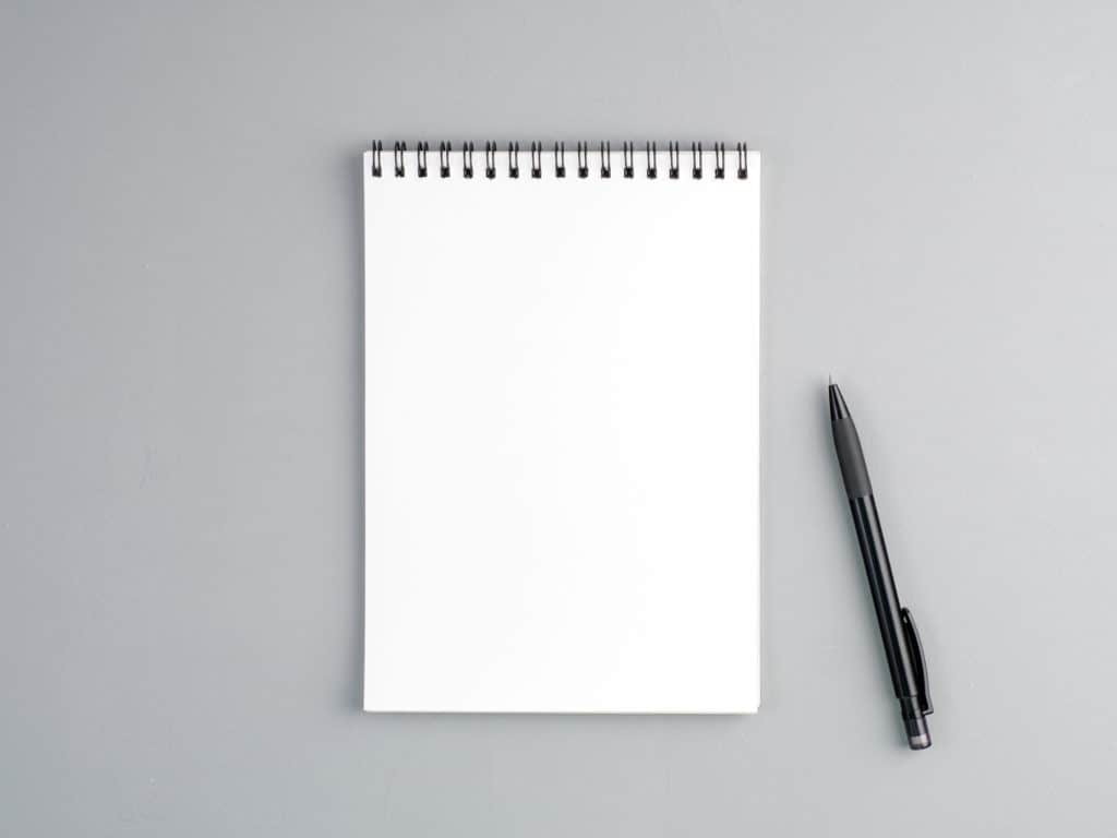 blank sheet of notebook with a spiral and pen on a neutral gray textured  background